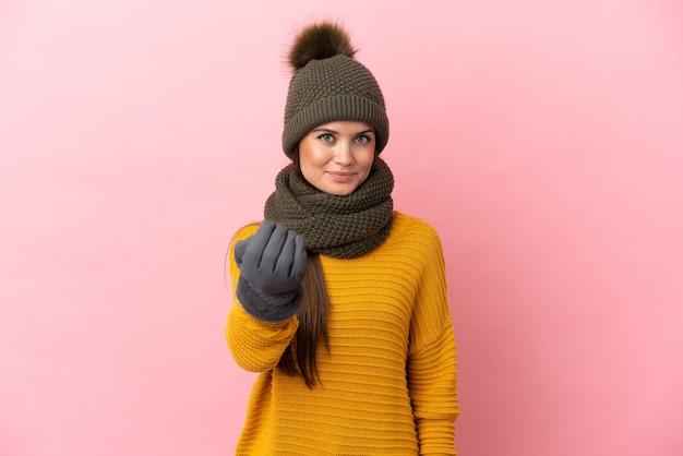Молодая кавказская девушка в зимней шапке изолирована на розовом фоне, приглашая прийти с рукой. счастлив что ты пришел