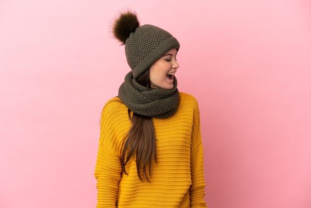 Молодая кавказская девушка в зимней шапке изолирована на розовом фоне, смеясь в боковом положении