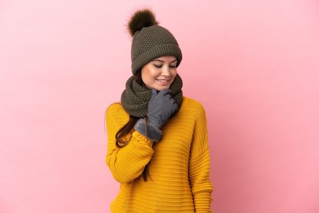 겨울 모자와 젊은 백인 여자는 측면을보고 웃 고 분홍색 배경에 고립