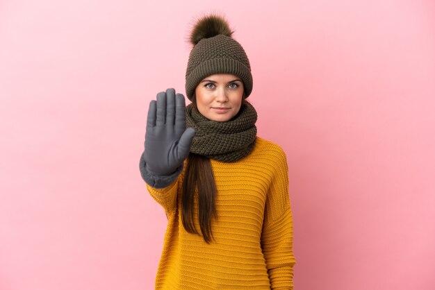 중지 제스처를 만드는 분홍색 배경에 고립 된 겨울 모자와 젊은 백인 여자