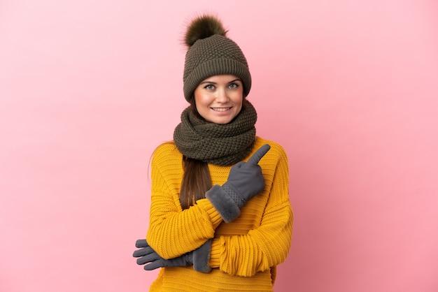 Молодая кавказская девушка в зимней шапке изолирована на розовом фоне, указывая в сторону, чтобы представить продукт
