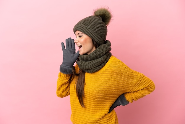 ピンクの背景に分離された冬の帽子を持つ若い白人の女の子は、横に大きく開いた口で叫んでいます