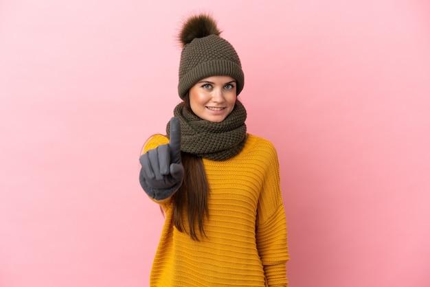 Молодая кавказская девушка в зимней шапке изолирована на розовом фоне, показывая и поднимая палец