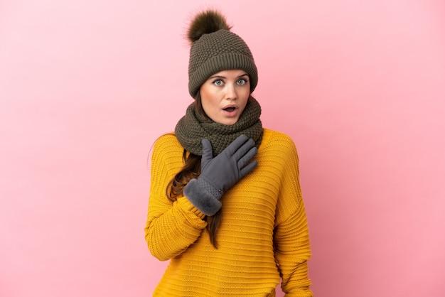 Молодая кавказская девушка в зимней шапке на розовом фоне удивлена и шокирована, глядя вправо