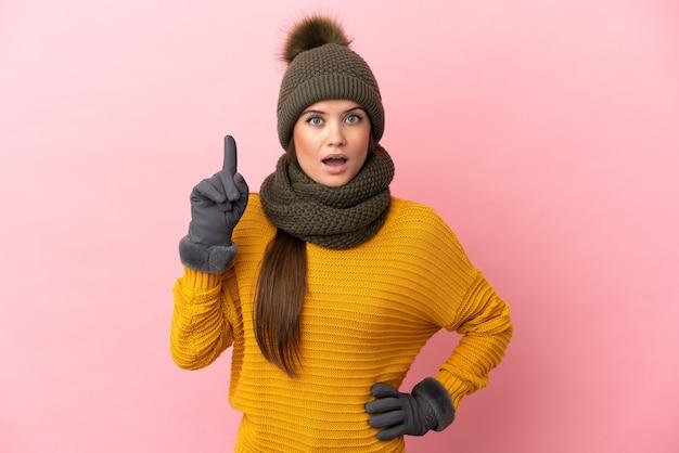 손가락을 가리키는 아이디어를 생각하는 분홍색 배경에 고립 된 겨울 모자와 젊은 백인 여자