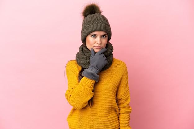 Молодая кавказская девушка в зимней шапке изолирована на розовом фоне мышления