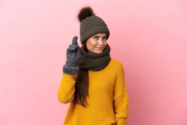 Молодая кавказская девушка в зимней шапке изолирована на розовом фоне со скрещенными пальцами и желает лучшего