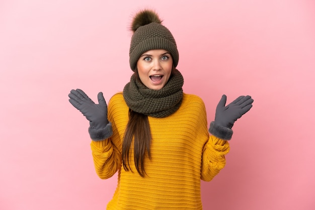 Молодая кавказская девушка в зимней шапке изолирована на розовом фоне с шокированным выражением лица