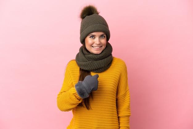 Молодая кавказская девушка в зимней шапке изолирована на розовом фоне с удивленным выражением лица