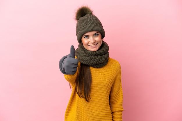 Молодая кавказская девушка в зимней шапке изолирована на розовом фоне с большими пальцами руки вверх, потому что произошло что-то хорошее