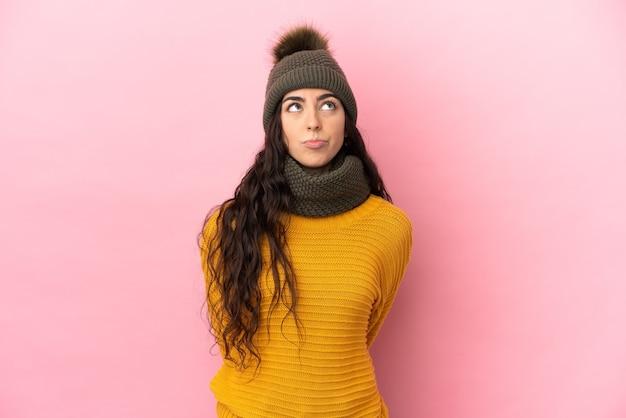 Молодая кавказская девушка в зимней шапке изолирована на фиолетовом фоне и смотрит вверх