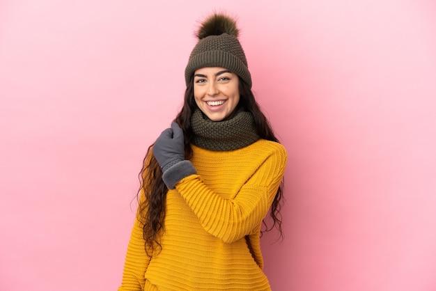 勝利を祝う紫色の背景に分離された冬の帽子を持つ若い白人の女の子