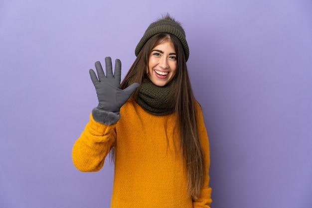 손가락으로 5 세 보라색 배경에 고립 된 겨울 모자와 어린 백인 소녀