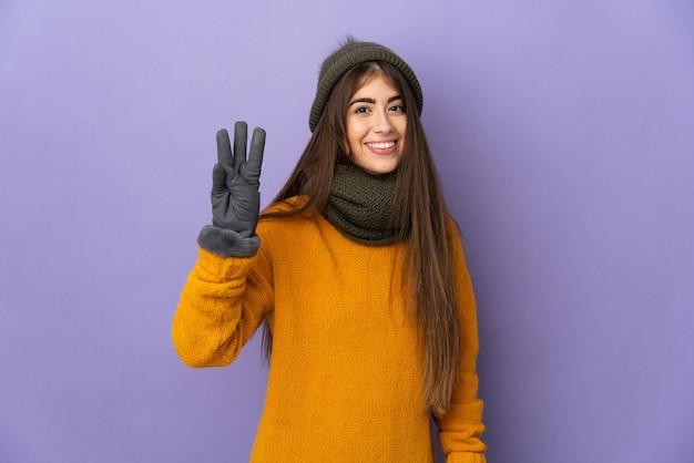 겨울 모자와 젊은 백인 여자는 보라색 배경에 행복하고 손가락으로 세 세에 고립