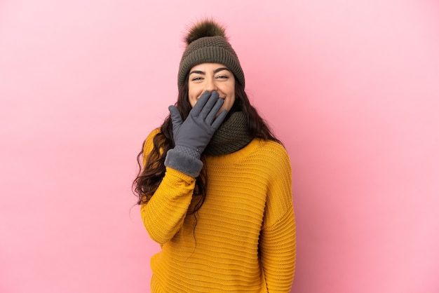 Молодая кавказская девушка в зимней шапке изолирована на фиолетовом фоне, счастливая и улыбающаяся, прикрывая рот рукой