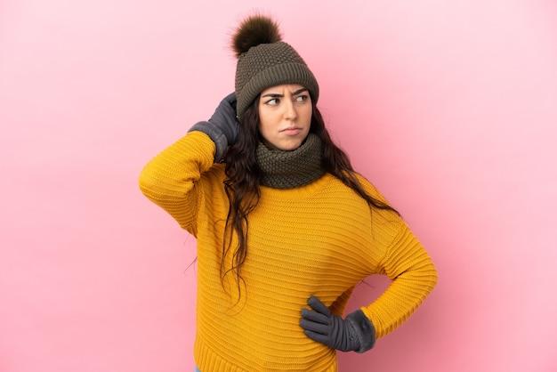 Молодая кавказская девушка в зимней шапке изолирована на фиолетовом фоне, сомневаясь