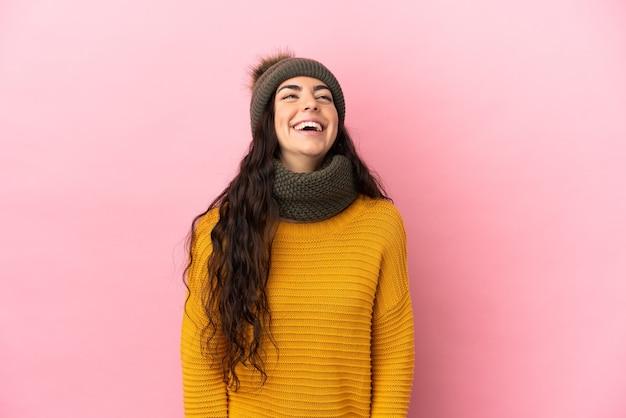 Молодая кавказская девушка в зимней шапке изолирована на фиолетовом фоне смеясь