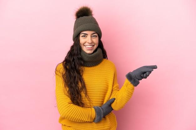 Молодая кавказская девушка в зимней шапке изолирована на фиолетовом фоне, указывая пальцем в сторону