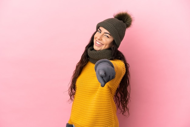 Молодая кавказская девушка в зимней шапке изолирована на фиолетовом фоне, указывая спереди со счастливым выражением лица