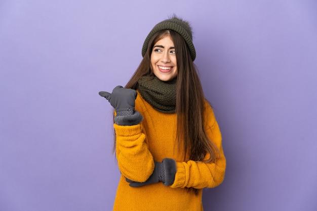 제품을 제시하기 위해 측면을 가리키는 보라색 배경에 고립 된 겨울 모자와 젊은 백인 여자