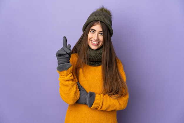 Молодая кавказская девушка в зимней шапке изолирована на фиолетовом фоне, указывая на отличную идею