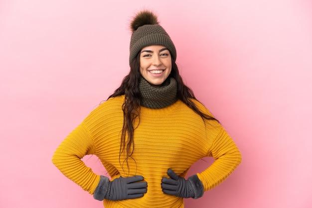 Молодая кавказская девушка в зимней шапке изолирована на фиолетовом фоне, позирует с руками на бедрах и улыбается