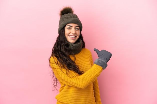 Молодая кавказская девушка в зимней шапке изолирована на фиолетовом фоне, гордая и самодовольная