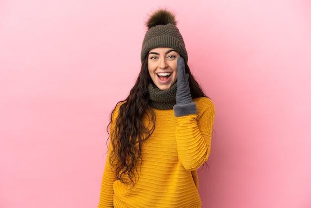 입 벌리고 외치는 보라색 배경에 고립 된 겨울 모자와 젊은 백인 여자