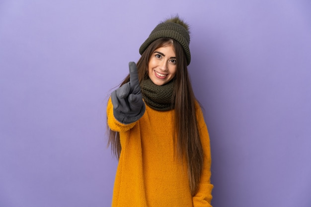 겨울 모자와 젊은 백인 여자는 보라색 배경에 표시 하 고 손가락을 들어 절연