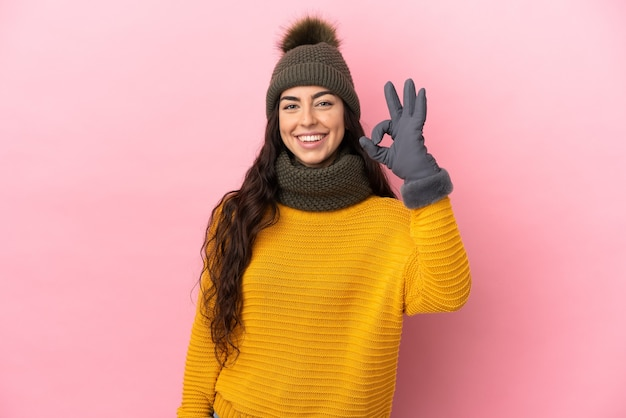 Молодая кавказская девушка в зимней шапке изолирована на фиолетовом фоне, показывая пальцами знак ок