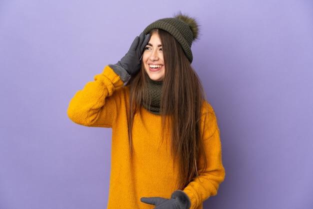 많이 웃 고 보라색 배경에 고립 된 겨울 모자와 젊은 백인 여자