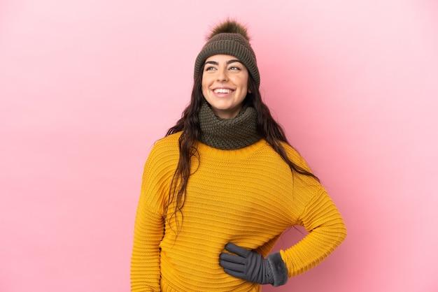 Молодая кавказская девушка в зимней шапке изолирована на фиолетовом фоне, думая об идее, глядя вверх