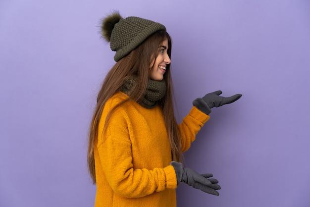 Молодая кавказская девушка в зимней шапке изолирована на фиолетовом фоне с удивленным выражением лица, глядя в сторону