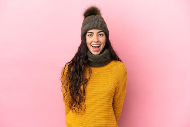 Молодая кавказская девушка в зимней шапке изолирована на фиолетовом фоне с удивленным выражением лица