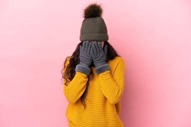 Молодая кавказская девушка в зимней шапке изолирована на фиолетовом фоне с усталым и больным выражением лица