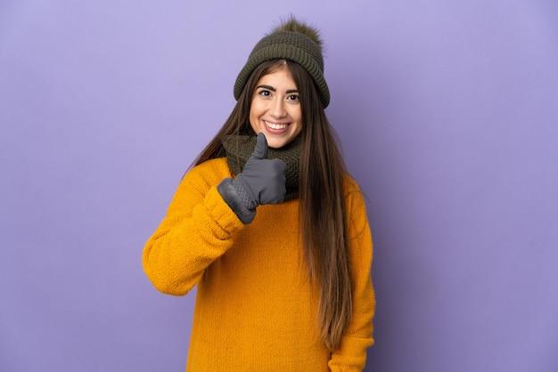 親指を立てるジェスチャーを与える紫色の壁に隔離された冬の帽子を持つ若い白人の女の子