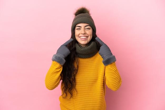 제스처를 엄지 손가락을주는 보라색 벽에 고립 된 겨울 모자와 젊은 백인 여자