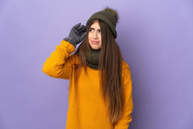 Молодая кавказская девушка в зимней шапке изолирована на фиолетовой стене, сомневаясь