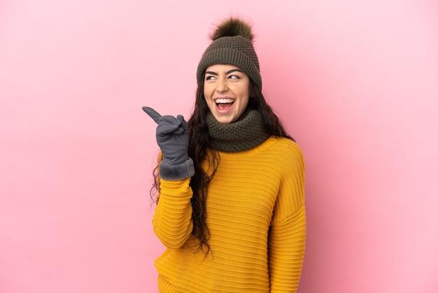 손가락을 들어 올리는 동안 솔루션을 실현하려는 보라색 벽에 고립 된 겨울 모자와 어린 백인 소녀