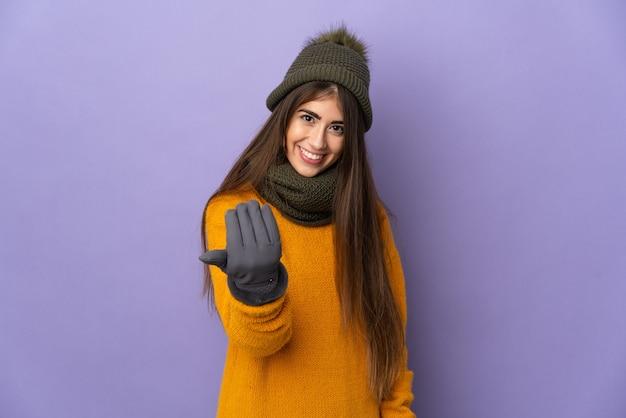 Молодая кавказская девушка в зимней шапке изолирована на фиолетовой стене, приглашая прийти с рукой. счастлив что ты пришел