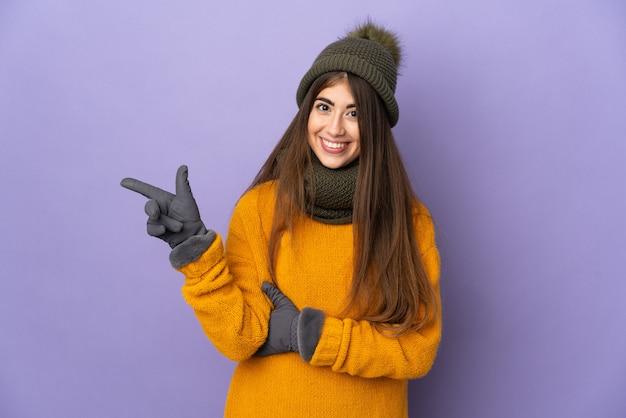 Молодая кавказская девушка в зимней шапке изолирована на фиолетовой стене, указывая пальцем в сторону