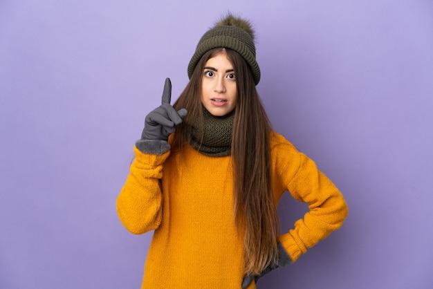 Молодая кавказская девушка в зимней шапке изолирована на фиолетовой стене, думая об идее, указывая пальцем вверх
