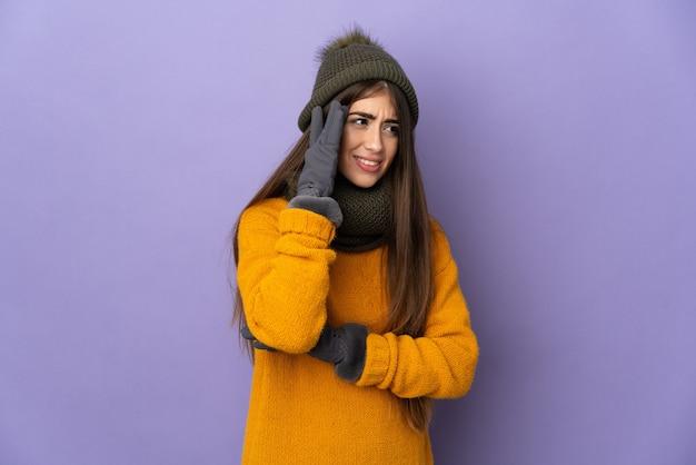 Молодая кавказская девушка в зимней шапке изолирована на фиолетовой стене с головной болью
