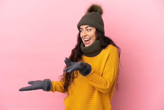 측면을 보는 동안 놀라운 표정으로 보라색 벽에 고립 된 겨울 모자와 젊은 백인 여자