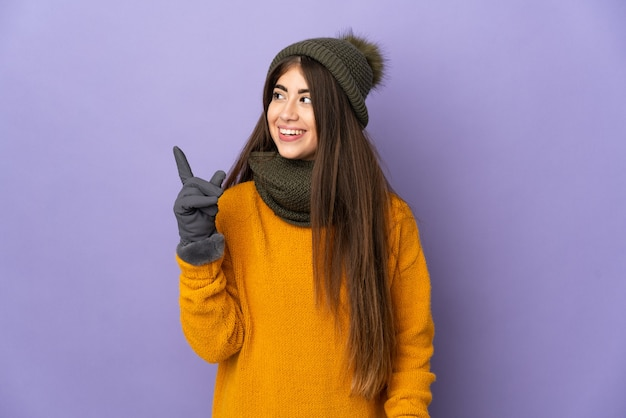 Young caucasian girl with winter hat isolated on purple background intending to realizes the solution while lifting a finger up