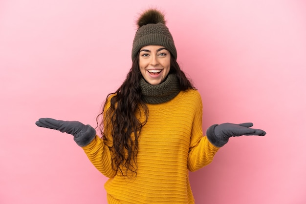 Young caucasian girl with winter hat isolated on purple background with shocked facial expression