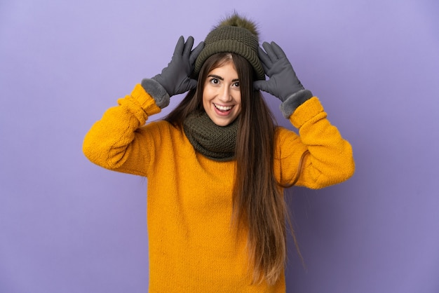 Young caucasian girl with winter hat isolated on purple wall with surprise expression