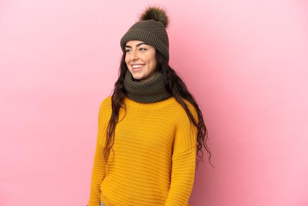Молодая кавказская девушка в зимней шапке изолирована