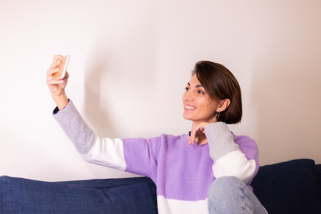 Young caucasian girl woman in bedroom on sofa look at mobile phone  camera