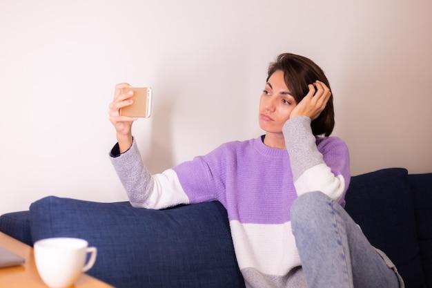 Giovane donna caucasica ragazza in camera da letto sul divano guarda la fotocamera del telefono cellulare